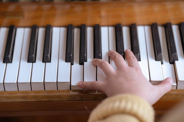 small handed pianist is playing large chords with small hands